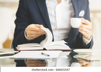 Businessman drinking coffee and reading book at workplace/in modern office. Close up, Education concept