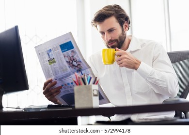 Businessman drinking coffee and reading newspaper in the office