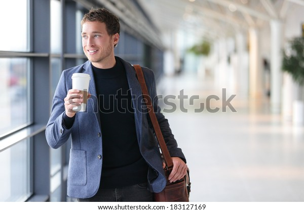 Businessman drinking coffee walking in airport. Casual urban professional smiling happy wearing suit jacket holding disposable coffee cup on travel. Handsome male model in his twenties.