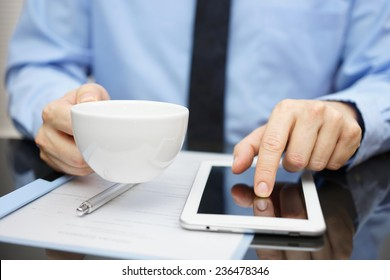 businessman is drinking coffee and working on tablet computer