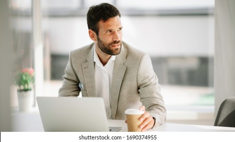 Businessman drinking coffee. Young handsome man drinking coffe and working.