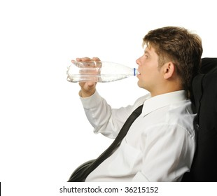 The businessman drinking water from a bottle. It is isolated on a white background