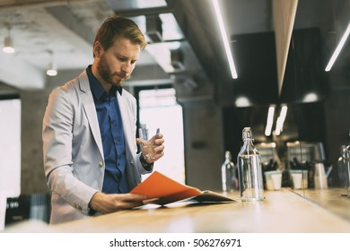 Businessman drinking water and reading paper during break