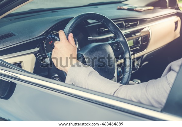 Businessman driving the luxury car on his morning commute to work. The handsome man's hand touched the steering wheel of his automobile with confidence in his road trip.