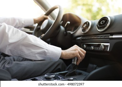 Businessman driving to work, hand shifting the gear stick