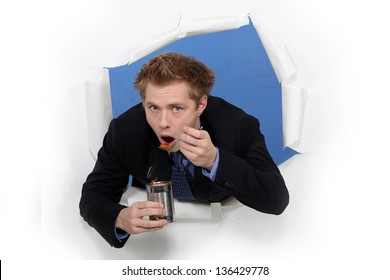 Businessman eating beans from a tin