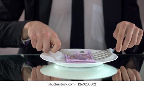 Businessman eating euro banknotes, squandering concept, embezzlement of budget