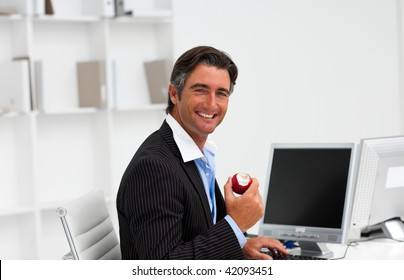Businessman eating a fruit at work and smiling at the camera