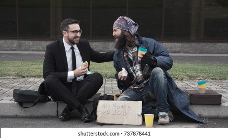 Businessman eating and talking with poor homeless man on pavement.