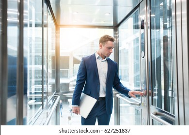 Businessman in elevator in the office center, looking to laptop