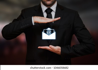 Businessman with email in envelope between his hands concept