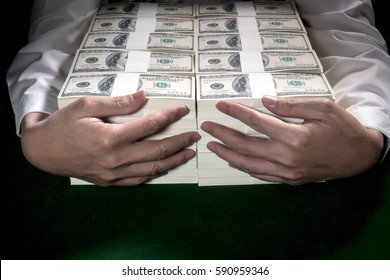 Businessman embrace 1 million US dollars in his arm.