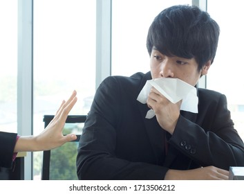 Businessman or employees sneezes or coughs and has symptoms of the disease - healthcare and medicine corna virus covid19 concept .