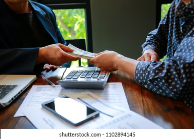 Businessman as an employer paying cash (dollar money) to worker at the office - wage, loan and bribery concepts