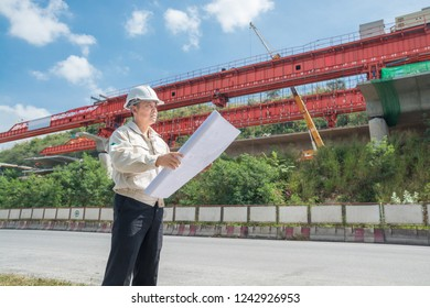 Businessman or Engineer or Architect wearing Hardhat and safety vest supervise Motorway or Highway Project Development holding Blueprint beside Infrastructure construction site