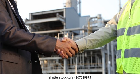 businessman and engineer handshake closing a deal in front of an large oil refinery