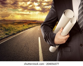 Businessman engineer holding blueprints of new architectural project standing on straight road. Concept of successful career start.