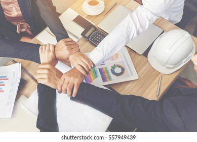 Businessman and engineer working  hands of business people joined hands together in office meeting. Teamwork Concept.