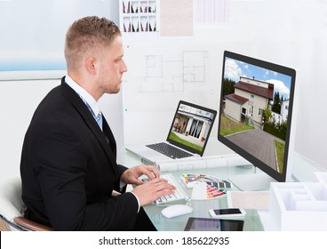 Businessman or estate agent checking a property portfolio online while sitting at his desk in the office looking at the exterior of a rural house visible on the desktop monitor