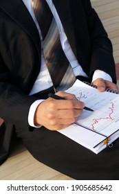 Businessman evaluates company data and checks charts and values
