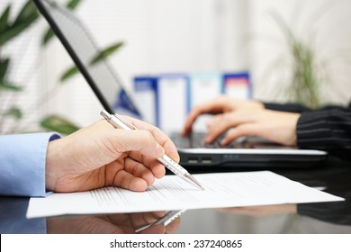 businessman is examine document and woman is working on laptop computer in background