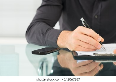 Businessman examines a contract and writing on paper