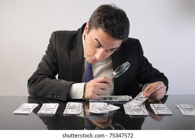 Businessman examining some banknotes through a magnifying glass
