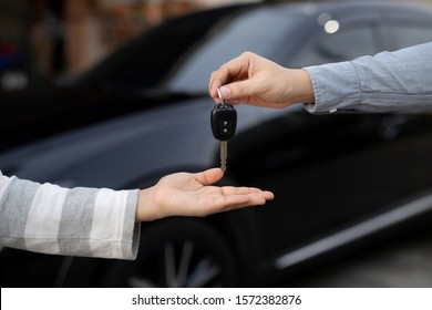 businessman exchange handing over the car keys for to a young women.