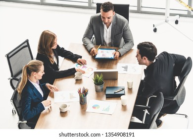 Businessman executive in group meeting discussion with other businessmen and businesswomen in modern office with coffee cups and documents on table. People corporate business working team concept.
