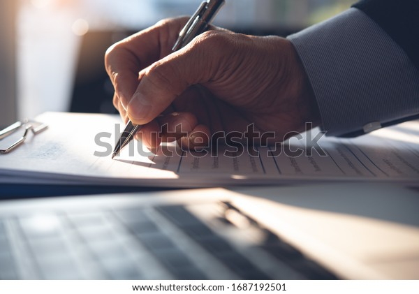 Businessman, executive manager hand filling paper business document, signing contract, partnership agreement and working on laptop computer on desk in modern office, close up