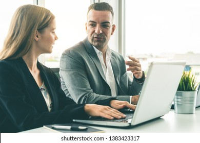 Businessman executive is in meeting discussion with a businesswoman worker in modern workplace office. People corporate business team concept.