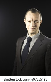 Businessman executive in suit, shirt and tie formal clothing aged in 40's against plain studio portrait background.