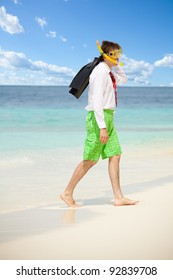 Businessman exiting the water wearing snoring mask with flippers and wearing formal clothes with red tie entering water on the beach