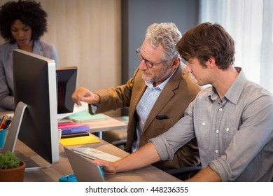 Businessman explaining colleagues over computer in office
