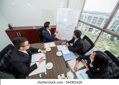 Businessman explaining diagrams on whiteboard during the meeting