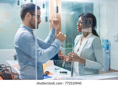 Businessman explaining financial oscillations to colleague in office.