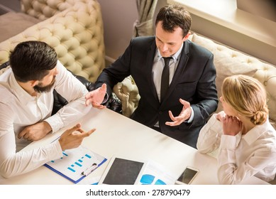 Businessman explaining a financial plan to colleagues at meeting.