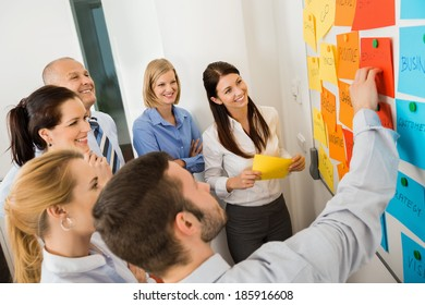 Businessman explaining labels on whiteboard to colleagues in meeting