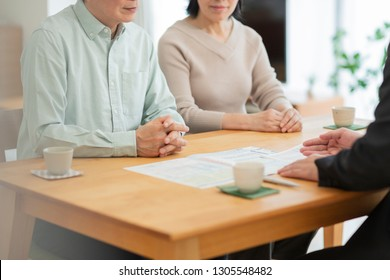 A businessman explaining to a middle-aged couple