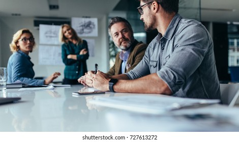 Businessman explaining new business ideas to peers. Business people discussing in board room.