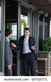 Businessman explaining something to his colleague, standing near building entrance