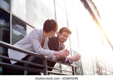 Businessman explains something to businesswoman on balcony