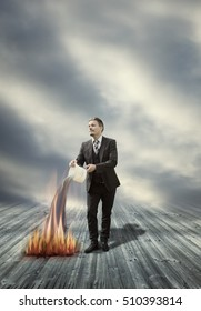 Businessman is Extinguishing Fire with Water - Keep Cool in Difficult Situation