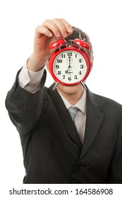 Businessman with face covered by red alarm clock.
