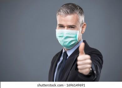 Geschäftsmann in Gesichtsmaske als Schutz gegen das Covid-19 oder Corona-Virus, das eine Daumen-up Geste in einem Kopf und Schultern Porträt auf Grau