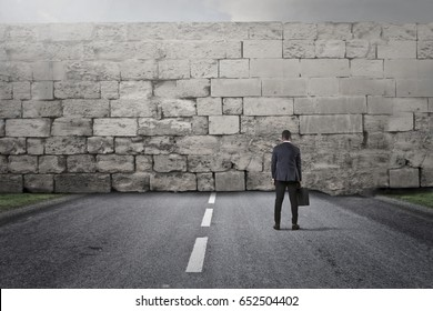 Businessman facing a big stone wall