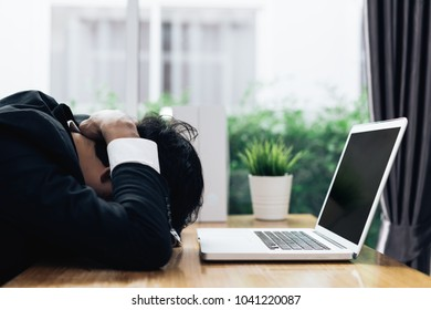 Businessman failure project plan deadline serious emotion and depression or deadline at office room with laptop computer report on working table