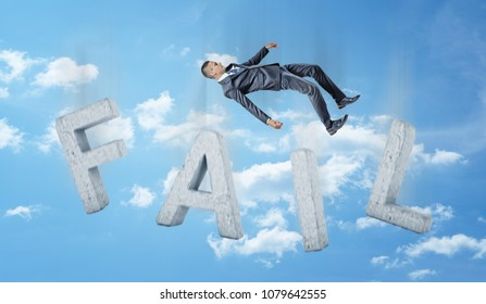 A businessman falling down in the sky on concrete letters forming a word FAIL. Business and work. Loss and failure. Corporate world.