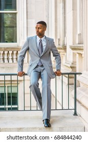 Businessman Fashion in New York. Young African American Man wearing light gray suit, white undershirt, tie, wristwatch, sitting on railing in vintage style office building, looking away, thinking.