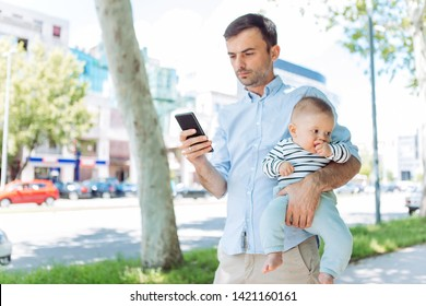 Businessman father and baby son on city street, father carrying son and using mobile phone